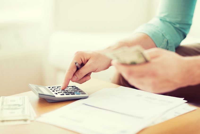 woman carrying cash and using calculator